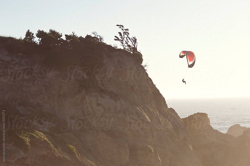 Paraglider flying out over the cape by neongrounds for Stocksy United