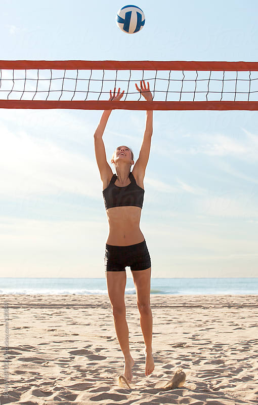 Beach volleyball. Sporty woman playing in sunny day.  by BONNINSTUDIO for Stocksy United