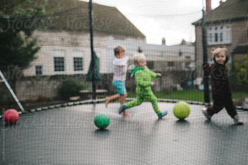 Three children are seen out of focus as the run around a trampoline. by Julia Forsman for Stocksy United