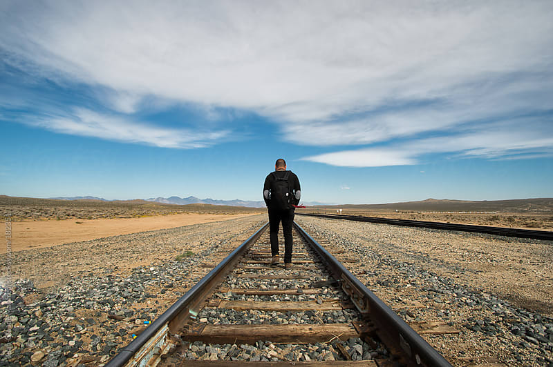 Backpacker walking along a railway in a desert landscape by Jean-Claude Manfredi for Stocksy United