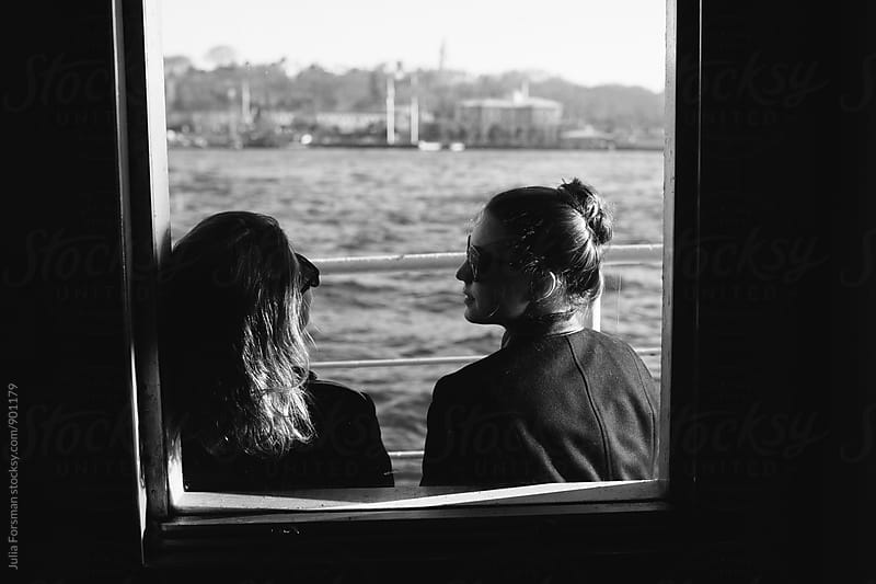 Two women in conversation as they travel by ferryboat on the Bosphorus. by Julia Forsman for Stocksy United