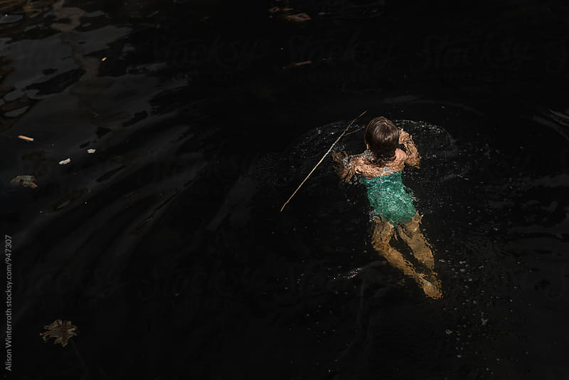 A Young Girl Swims In A Dark Lake by Alison Winterroth for Stocksy United