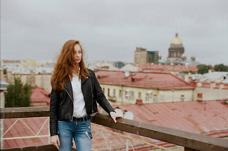 Woman standing on a roof with city view by Liubov Burakova for Stocksy United