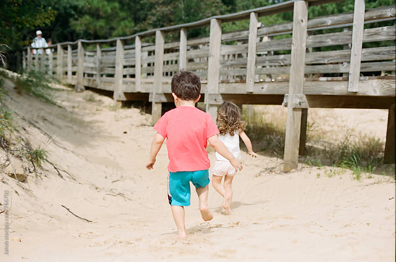 Two young children running after each other on a beach by Jakob for Stocksy United
