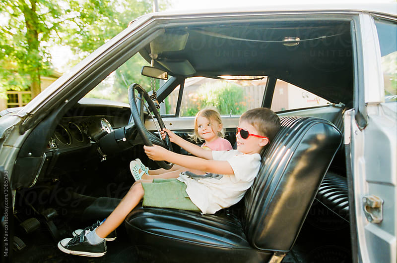 boy drives classic car by Maria Manco for Stocksy United