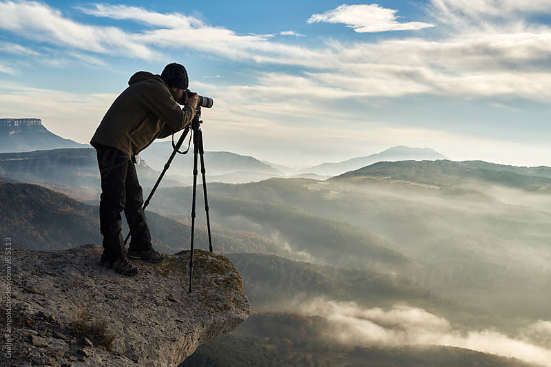 Photographer taking a picture on the edge of a cliff by Guille Faingold for Stocksy United