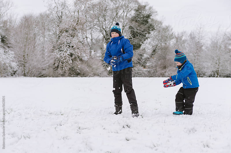 older brother prepares to throw snowball at viewer by Rebecca Spencer for Stocksy United