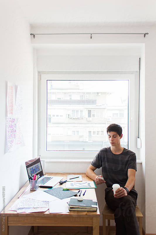 Modern urban teenage boy at using mobile phone next to working table by Nabi Tang for Stocksy United