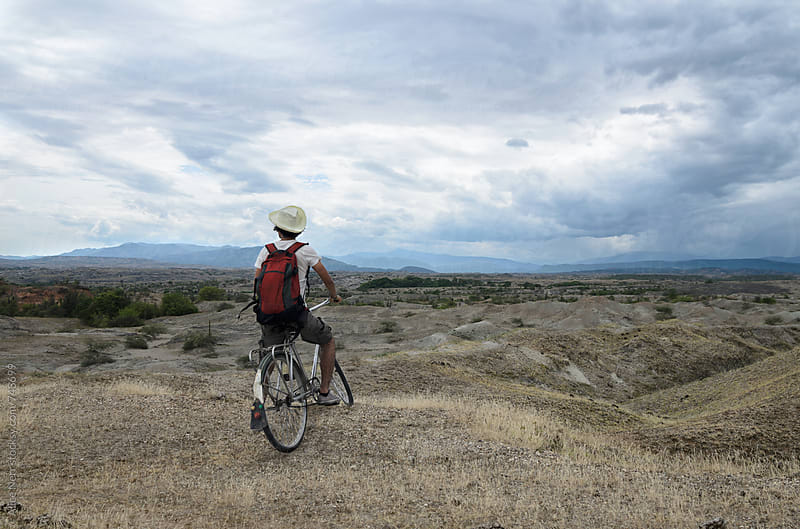 Back view of a traveler on a bicycle overlooking stunning prairie and mountains landscape  by Alice Nerr for Stocksy United