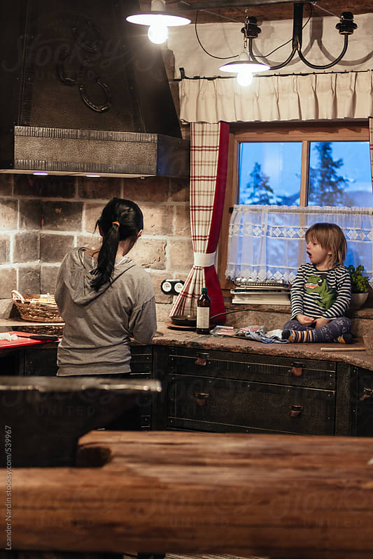 mother cooking in cast iron kitchen while son is watching by Leander Nardin for Stocksy United
