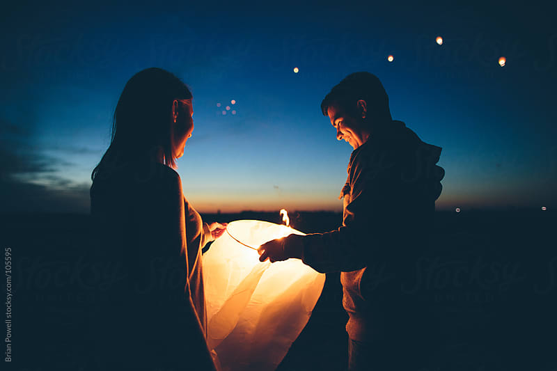 young couple lighting Chinese lanterns at twilight by Brian Powell for Stocksy United