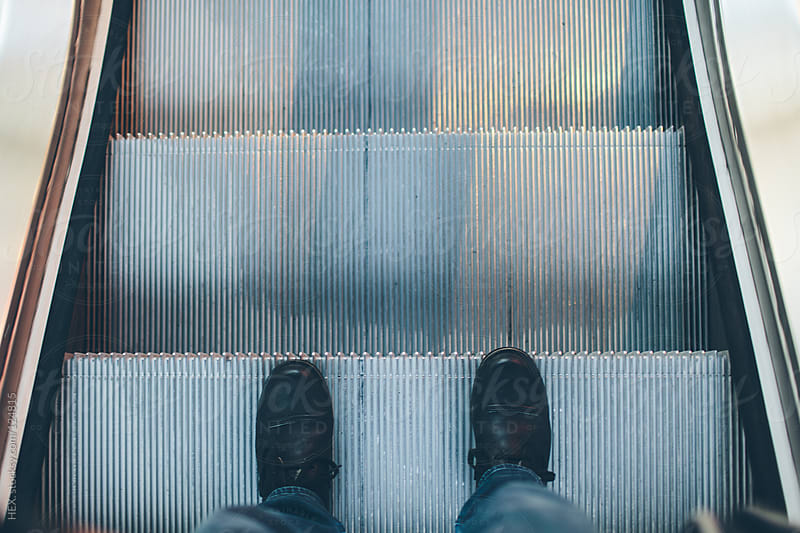 Feet on the escalator going down by HEX. for Stocksy United