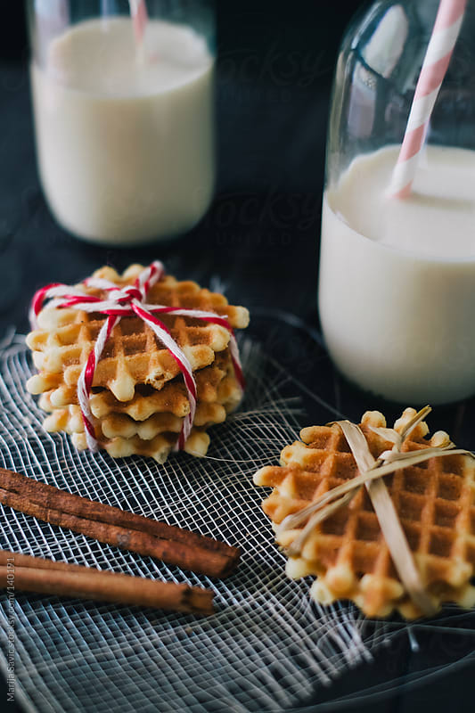 Fresh waffle, bottle of milk and cinnamon on wooden black table.  by Marija Savic for Stocksy United