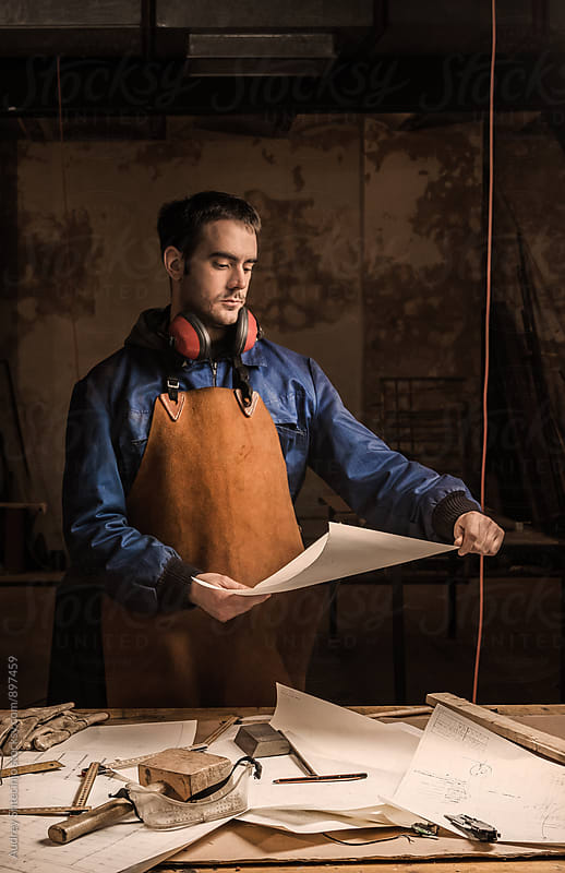 Young man working in his small workshop. by Audrey Shtecinjo for Stocksy United