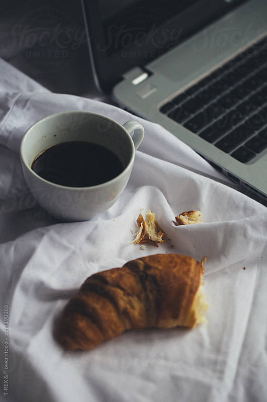 A croissant with coffee near the laptop by T-REX & Flower for Stocksy United