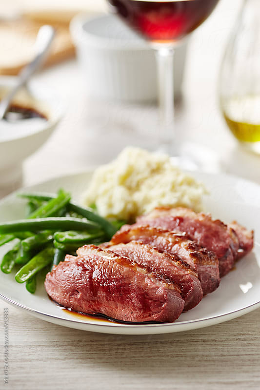 Sliced duck breast with mashed potato and green beans by Martí Sans for Stocksy United