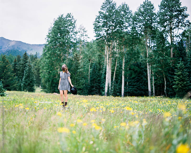 Woman standing in meadow by Daniel Kim Photography for Stocksy United