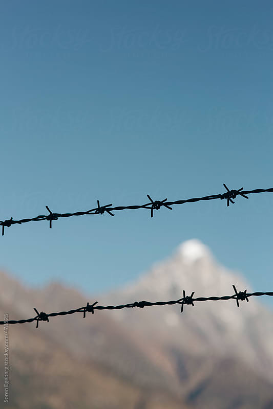 Barbed wire restricted access to mountains and wilderness area - Concept by Soren Egeberg for Stocksy United