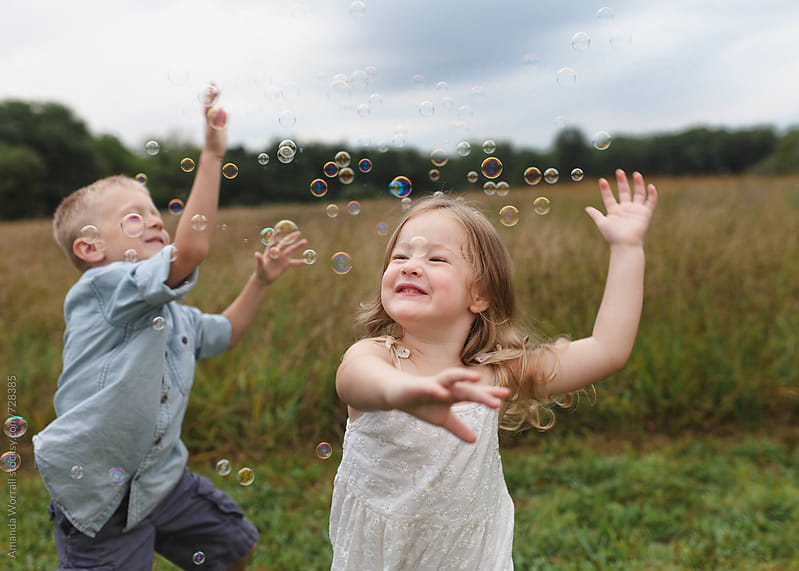 Brother and sister jump around trying to catch bubbles by Amanda Worrall for Stocksy United