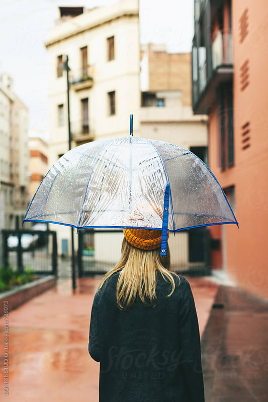 Anonymous woman with an umbrella in a rainy day. by BONNINSTUDIO for Stocksy United