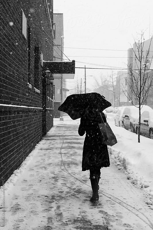 Woman walking through snowstorm. New York City. by Kristin Duvall for Stocksy United