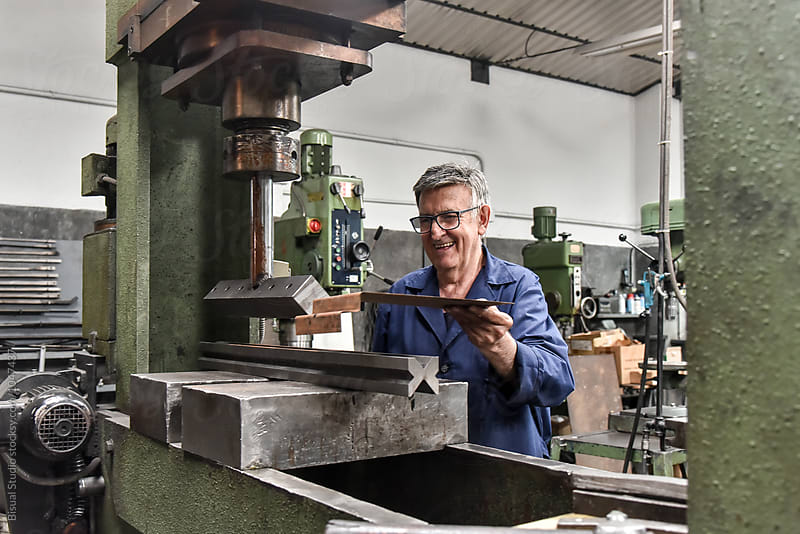 Senior man working with an hydraulic press by Bisual Studio for Stocksy United