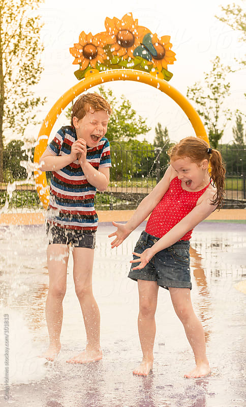 Children playing in a water play area by Craig Holmes for Stocksy United