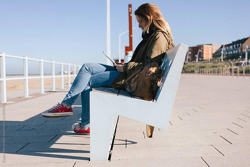 Student working on her tablet outside on a boulevard. by Koen Meershoek for Stocksy United