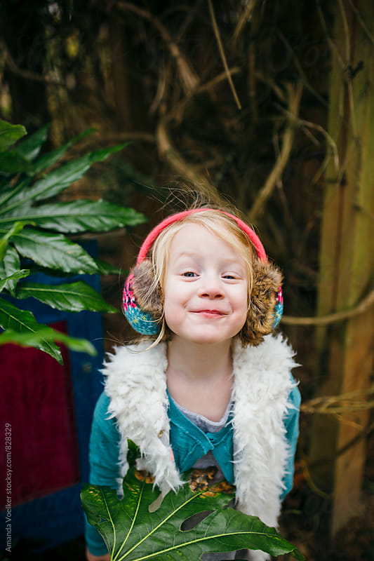 Little Girl Stands Among the Leaves, looking Cheekily at the camera by Amanda Voelker for Stocksy United