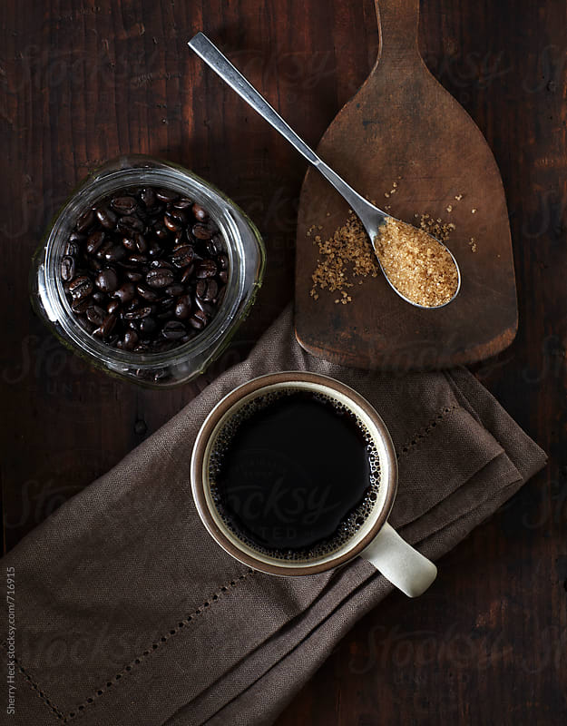 Coffee in mug with coffee beans and raw sugar overhead by Sherry Heck for Stocksy United