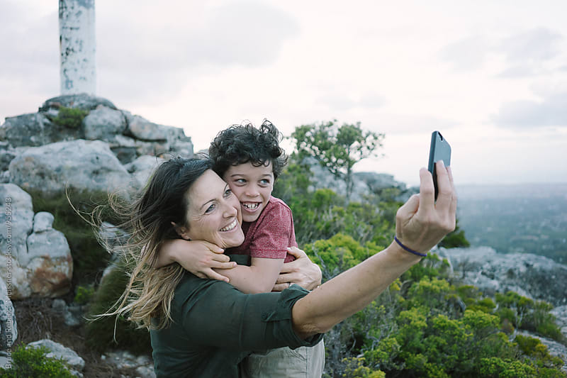 Mom and son selfie by Bruce and Rebecca Meissner for Stocksy United