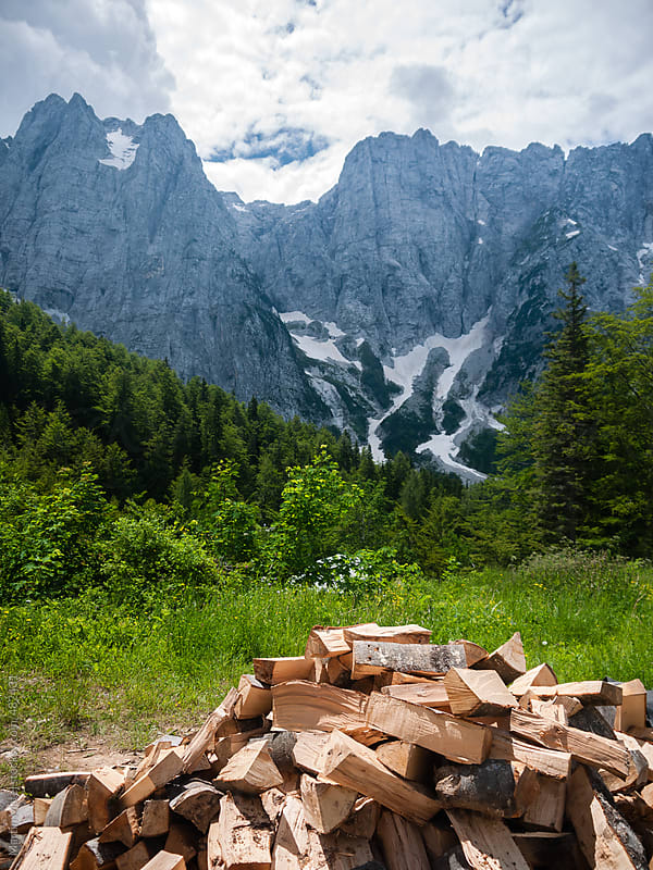 Pile of wood with rocks in the background by Martin Matej for Stocksy United