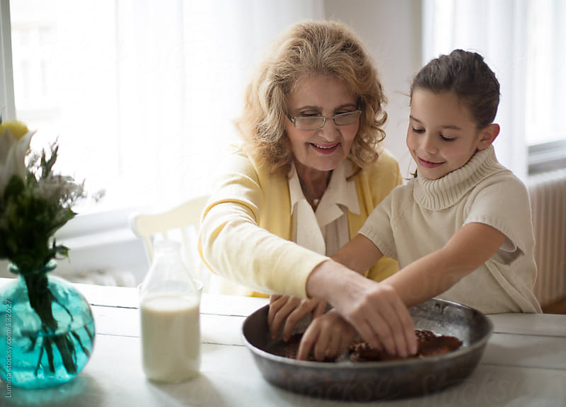 Grandma and Granddaughter Eating Cookies by Lumina for Stocksy United