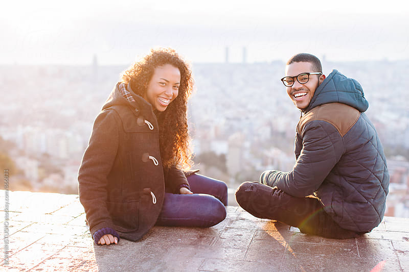 Smiling couple sitting together above city.  by BONNINSTUDIO for Stocksy United