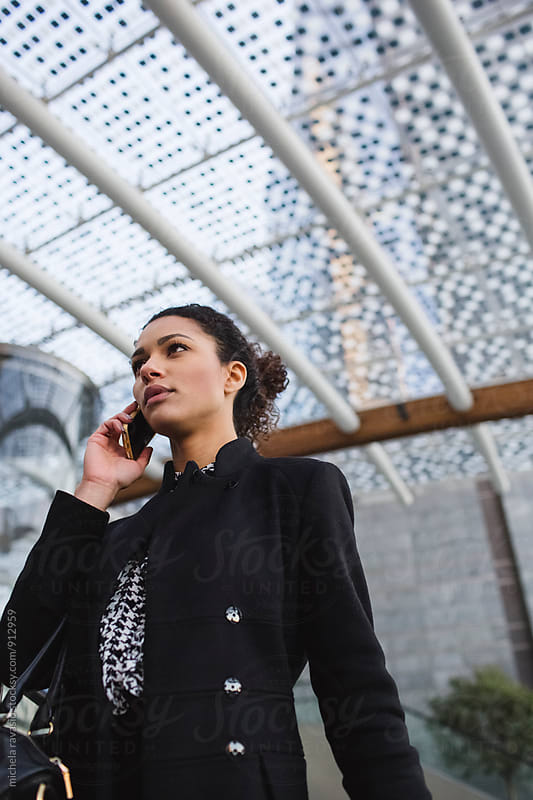 Attractive young businesswoman using her cell  by michela ravasio for Stocksy United