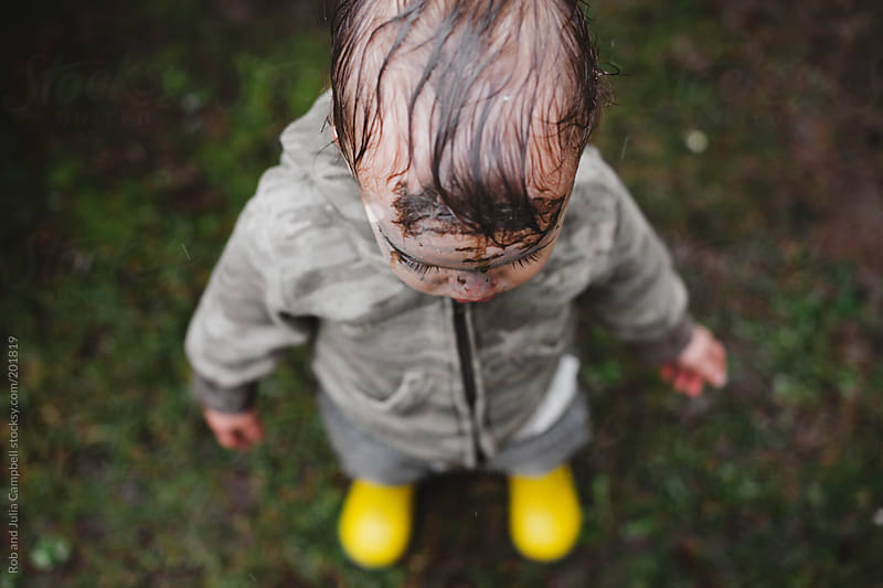 Cute young toddler boy outside in the rain with face covered in mud - funny by Rob and Julia Campbell for Stocksy United