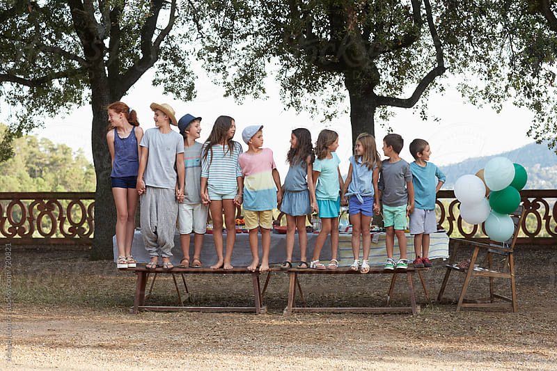 Group portrait of ten children holding hands and looking at each other by Miquel Llonch for Stocksy United