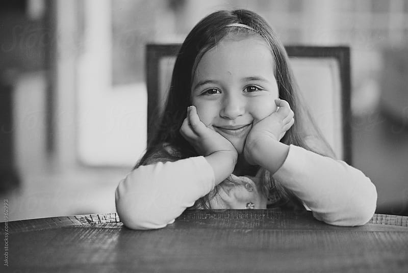 Black and white portrait of a cute young girl sitting at kitchen table with her face in her hands by Jakob for Stocksy United