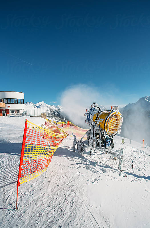 Snow canon producing artificial snow in the mountains in winter by Soren Egeberg for Stocksy United