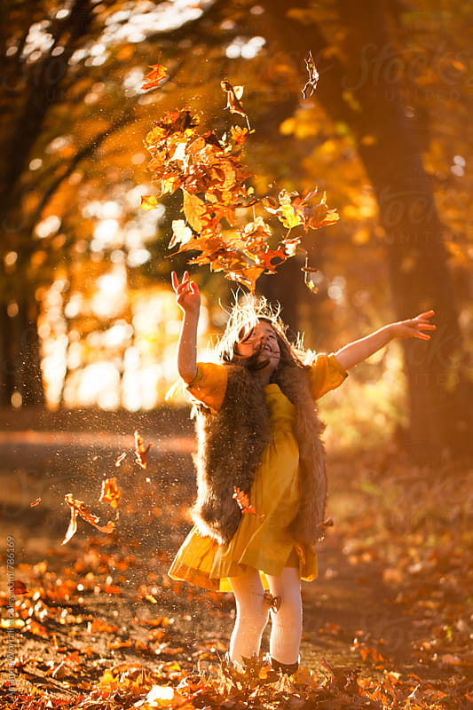 A smiling young girl tosses leaves in the air by Amanda Worrall for Stocksy United