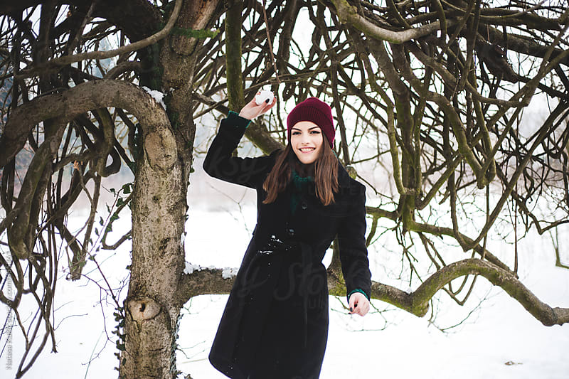 Winter portrait of a beautiful brunette throwing snowball by Natasa Kukic for Stocksy United