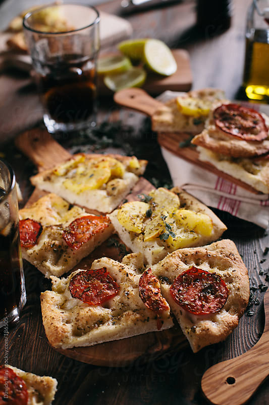 Italian Focaccia with potatoes and tomatoes by Davide Illini for Stocksy United