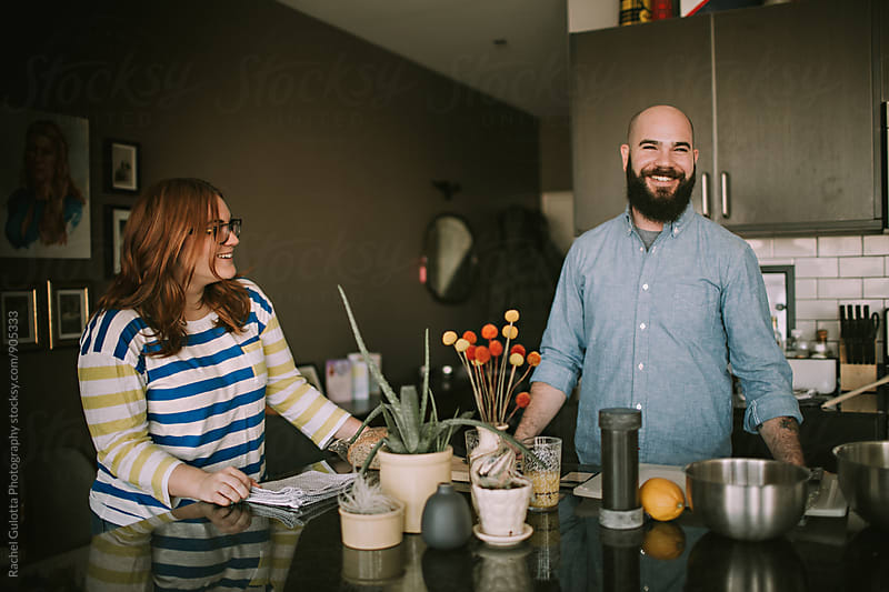 A Young Couple Hangs out and Laughs in Their Kitchen by Rachel Gulotta Photography for Stocksy United