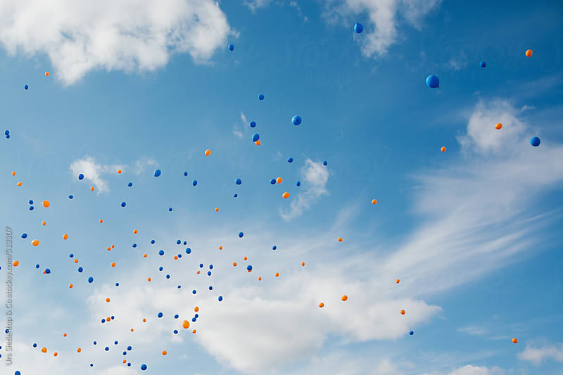 Blue and orange balloons in the sky by Urs Siedentop & Co for Stocksy United