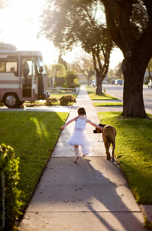 Girl in white dress with dog walking away on sidewalk in late day sunlight by Dina Giangregorio for Stocksy United