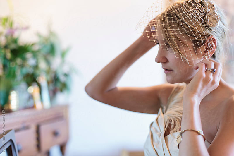 A beautiful woman adjusts the veil of her headpiece. by Holly Clark for Stocksy United