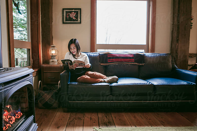Woman reading a magazine on her blue leather couch by Kristine Weilert for Stocksy United