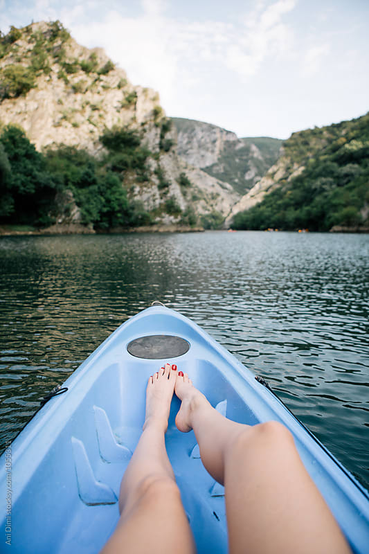 View of woman feet, while paddling a kayak on a lake by Ani Dimi for Stocksy United