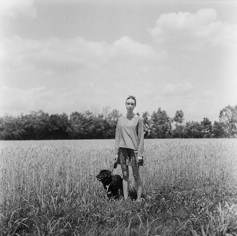 A portrait of a young beautiful woman with a black dog in a field by Anna Malgina for Stocksy United
