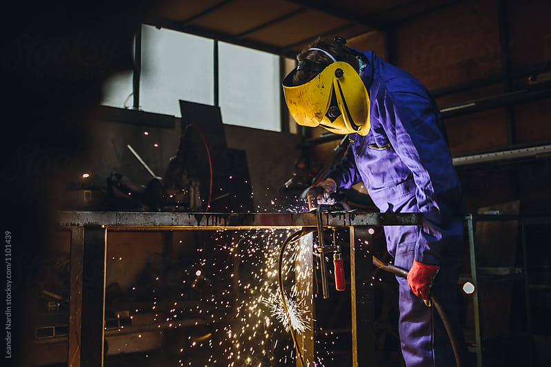 portrait of a metal worker with yellow protection mask operationg a plasma cutter by Leander Nardin for Stocksy United